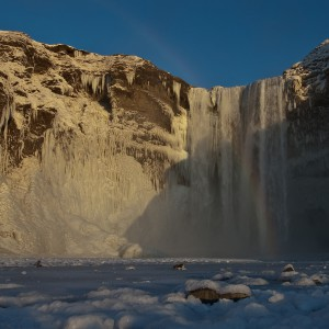 skogafoss waterfall frozen in iceland